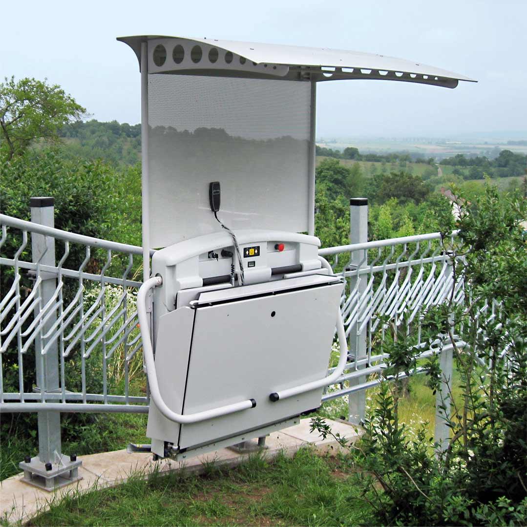 Plattformtreppenlift T80 im Außenbereich. Fahrschiene ca. 65 m durch den Garten und Plattform mit einem Dach.
